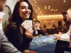 Girl with cards in her hands smiles at winning poker in a casino.